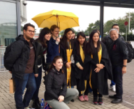 Photo by Susan Smulyan. Public Humans with four college graduates from Hong Kong who hold a yellow umbrella in remembrance of the Umbrella Movement.